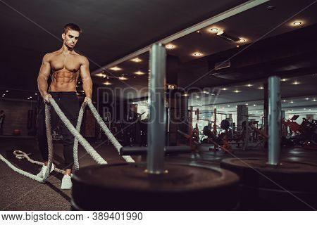 Fitness Man Working Out With Battle Ropes At Gym. Battle Ropes Fitness Man At Gym Workout Exercise F