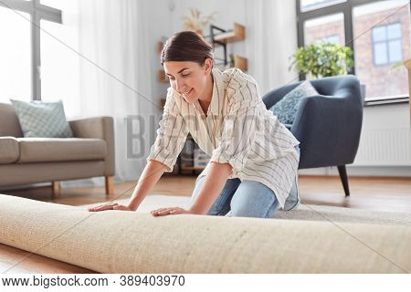 household, home improvement and interior concept - happy smiling young woman unfolding carpet