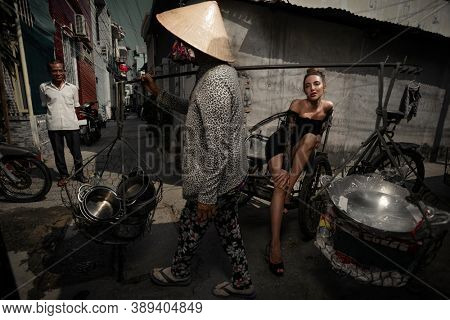 16 Jan. 2020 - Phan Thiet, Vietnam. Urban portrait of Young woman on tricycle on the slum against the background of Vietnamese residents, a street vendor and a random passerby
