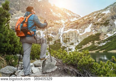 Man hiker, hiking backpacker traveler camper walking on the top of mountain in sunny day under sun light. Beautiful mountain landscape view.