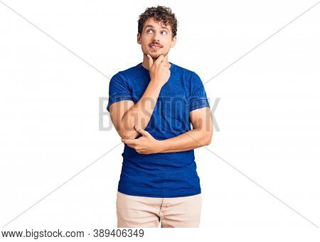 Young handsome man with curly hair wearing casual clothes with hand on chin thinking about question, pensive expression. smiling with thoughtful face. doubt concept.