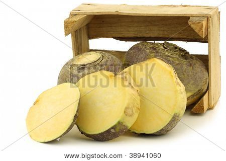 fresh turnip(brassica rapa rapa) and a cut one in a wooden crate on a white background