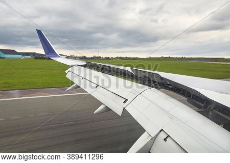 Airplane wing with flaps and spoilers fully extended to slow down the aircraft after landing