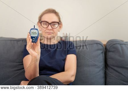 Caucasian Woman Holding Glucose Meter. Middle Aged Health. Hyperglycemia Concept.