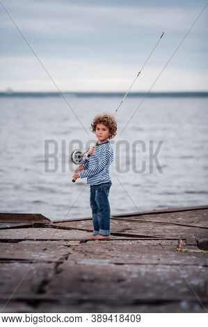 Cute Curly-haired Kid Fisherman Stands On Concrete Pier With A Vintage Fly-fishing Rod And Reel. Sum