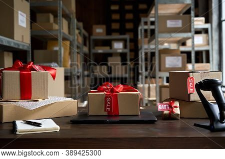 Table With Laptop And Gift Boxes With Sale Tags On Table In Warehouse. Online Ecommerce Retail Busin