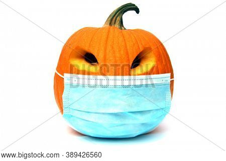 Halloween Pumpkin. Halloween Jack O Lantern with a Paper Face Mask. Isolated on white. Room for text. Coronavirus is dangerous, wear your mask!