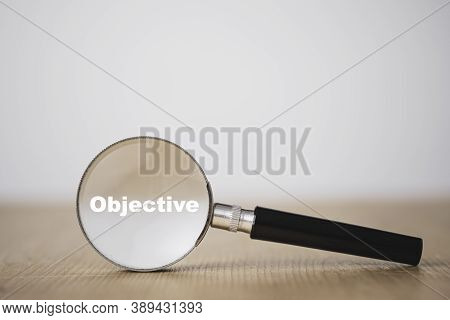Business Objective Target And Goal Concept, Objective Wording On Magnifier Glass On Table.