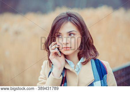 Phone Talk. Closeup Portrait. Serious Woman Talking On Mobile Phone Outside Outdoors On Autumn Park