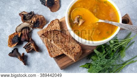 Mushroom Soup With Porcini Mushrooms On A On A Wooden Board On A Grey Background. Nearby Lies Toast