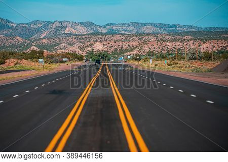 Panorama View Of An Endless Straight Road Running Through The Barren Scenery Of The American Southwe