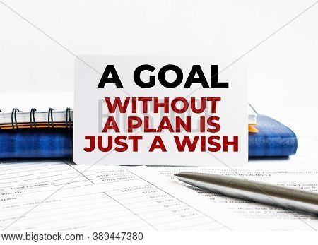Business Card With Text A Goal Without A Plan Is Just A Wish Lying On Blue Notebook