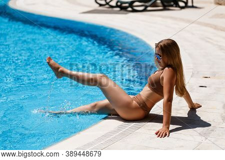 Beautiful Slim Sexy Young Woman With Long Blond Hair In A Beige Swimsuit Resting Near The Pool With