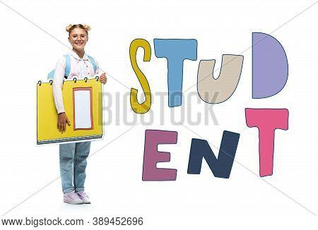 Length View Of Joyful Schoolchild In Eyeglasses Holding Paper Cut Notebook Near Student Lettering On