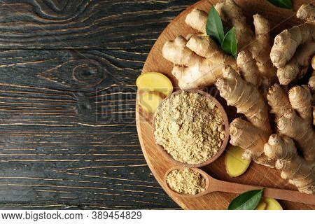 Board With Ginger And Ginger Powder On Wooden Background