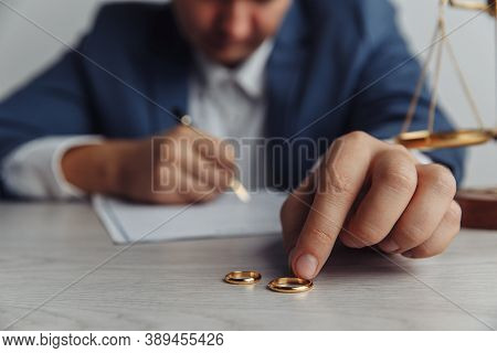 Frustrated Husband Signing Divorce Contract. Mans Hand And Rings Close-up. Divorce And Separation Co
