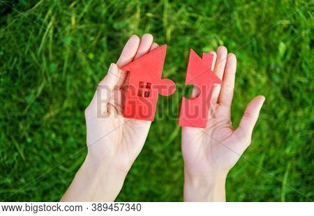 Red House With A Shape Of Two Parts Of Puzzle In Human Hands