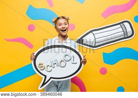 Schoolchild Holding Speech Bubble With School Lettering Near Multicolored Paper Elements And Pencil