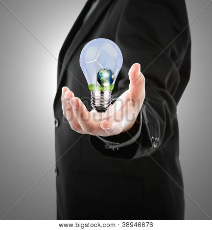 Business man holding  light bulb with  wind turbine and earth inside (Elements of this image furnished by NASA)