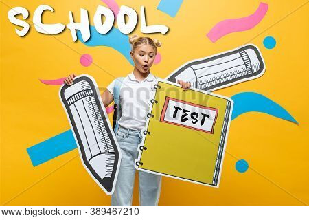 Schoolchild Holding Paper Notebook And Pencil Near School And Test Lettering On Yellow