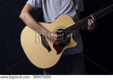 Musician Playing Acoustic Guitar In The Dark, At Night With Side Lighting.