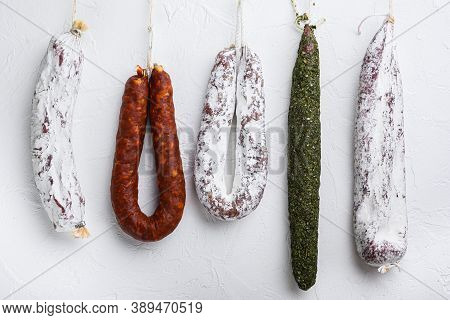 Traditional Dry Cured Sausages Meat Hanging On White Textured Background
