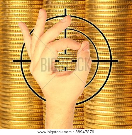 Hand And Target Against Coins Of Yellow Metal