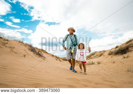 Father With Child Daughter In The Desert. Walk Through Desert In Oleshky Sands, Kherson Region, Ukra