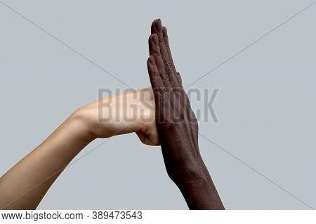 Two Hands, Black And White. A White Fist Hits A Black Palm.the Concept Of Inter-racial Friendship An