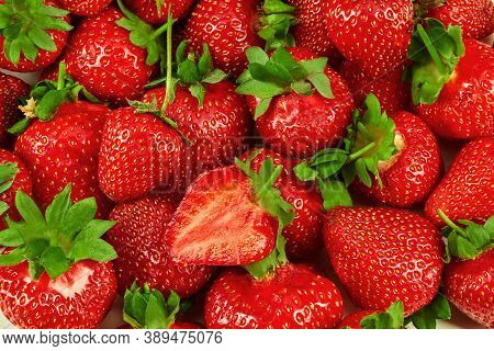 Lots Of Whole Red Tasty Strawberries And One Cut In Half, As A Background. Palatable Summer Harvest.