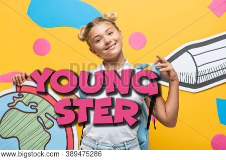 Holding Globe Maquette Touching Backpack Near Youngster Lettering, Paper Pencil And Colorful Element
