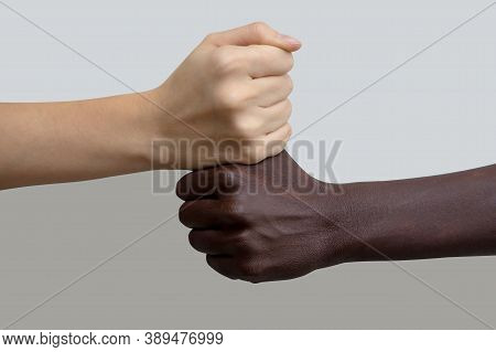 A White Hand In The Shape Of A Fist, Lying On Top Of A Dark-skinned Fist. Gray Isolated Background,