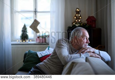 Lonely Senior Man Sitting On Sofa Indoors At Christmas, Solitude Concept.