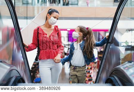 Mother And Daughter With Face Mask On Escalator Indoors In Shopping Center, Coronavirus Concept.
