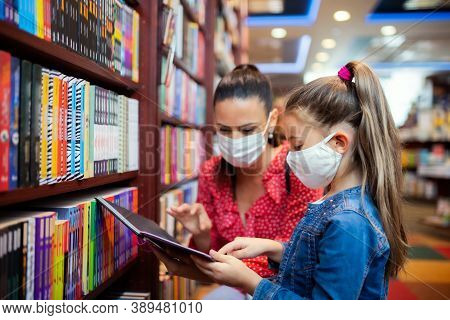 Mother And Daughter With Face Mask Shopping In Bookshop, Coronavirus Concept.