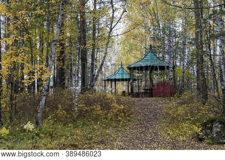 A Pavilion For Rest And Relaxation In The Autumn Forest. The Pavilion Has Green Roofs.