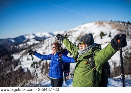 Senior Couple Hikers With Nordic Walking Poles In Snow-covered Winter Nature, Stretching Arms.