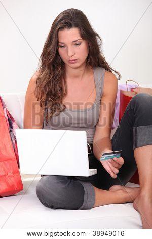 Brunette sat at home shopping on-line