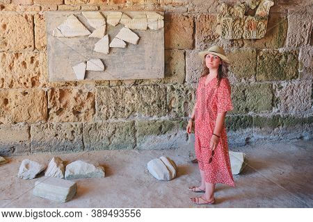 A Woman Among The Archaeological Site Anthony Terms, Board With Latin Inscriptions. The Ruins Of Car