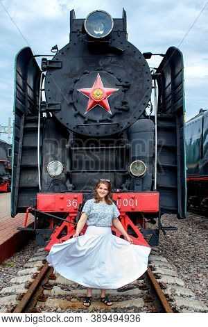 Young Woman With Billowing Dress Against The Background Of Steam Locomotive. Retro Train Of The Sovi