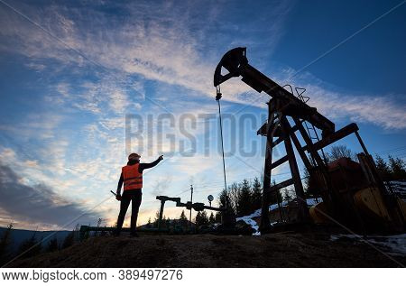 Back View Of Oil Man In Work Vest Standing Near Petroleum Pump Jack With Sunset On Background. Oil W