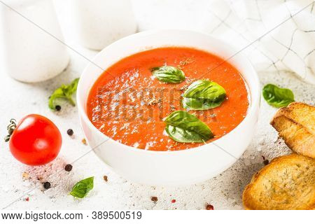 Tomato Soup With Basil At White Table. Summer Cold Vegan Dish.