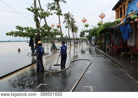 Hoi An, Vietnam, October 13, 2020: Workers Clear The Street's Mud Along The Thu Bon River After Seve