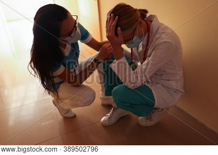 Nurse Calms Crying Doctor Wearing Medical Protective Mask In Bright Hospital Corridor. Psychological