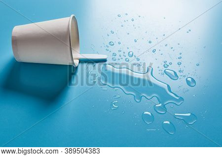 Dark Paper Cup With Abstract Drops Of Spilled Water On Blue Background. Spilled Alcohol Drink Cup Co
