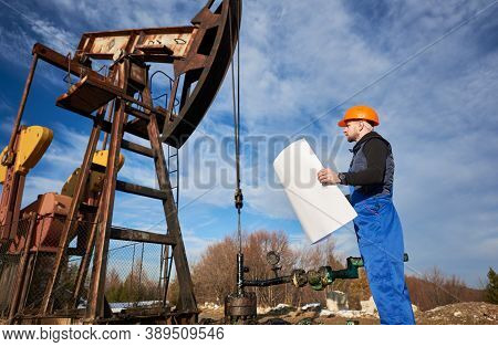 Side View Of Oil Worker Holding Plan Of Oil Field At Petroleum Pump Jack. Drill Operator In Work Uni