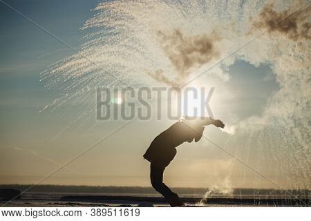 The Girl Has Fun In The Winter Splashes Boiling Water From The Thermos On The Strong Frost. The Conc