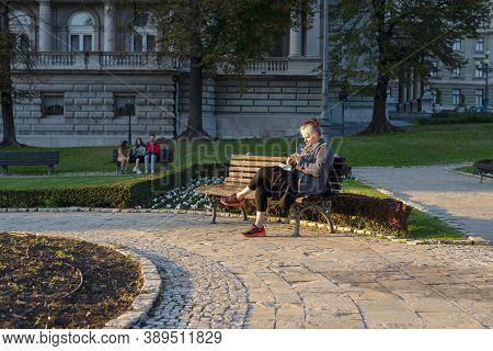 Belgrade, Serbia-10.10.2020. Old Woman On Bench With Cellphone. Pensioner Lifestyle. Senior Woman Us