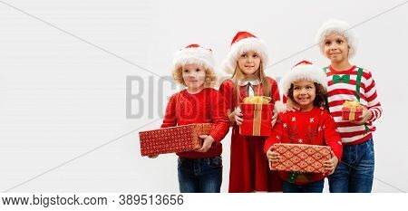 A Group Of Children With Christmas Gifts In Their Hands And In Holiday Costumes On A White Backgroun