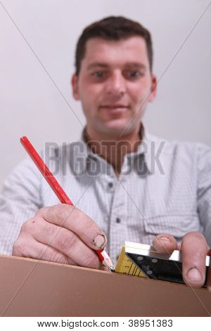 Closeup of a man measuring a piece of wood and marking it with a pencil